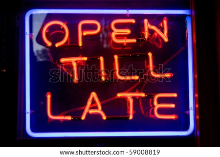 Blue and red neon sign of the words 'Open till late' inside a square of neon, on a black background. - stock photo