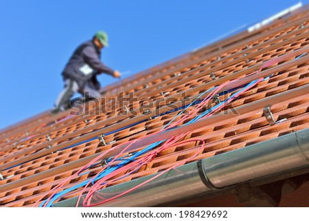 Blue and red photovoltaic cables on the roof with worker in the background. Soft front focus with shallow depth of field - stock photo
