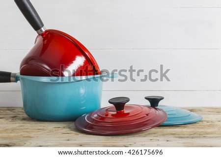 Blue and red saucepans with lids - stock photo