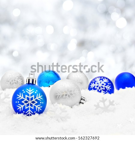 Blue and silver Christmas baubles in snow with silver light background - stock photo
