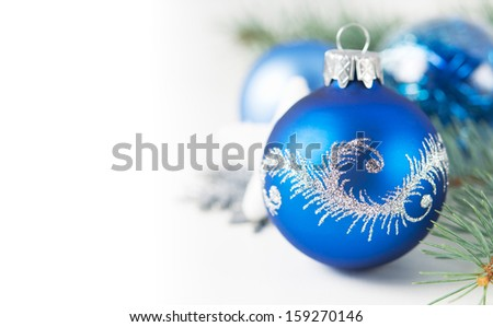 Blue and silver xmas ornaments on white background with copy space - stock photo