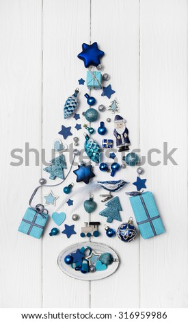 Blue and turquoise christmas tree of small miniatures on white wooden background for decoration.
