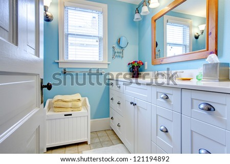 Blue and white bathroom with lots of storage space with open door. - stock photo