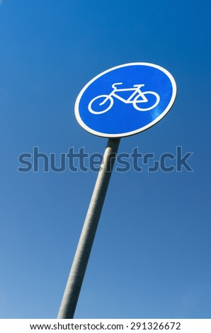 Blue and white bicycle road sign on the blue sunny sky - stock photo