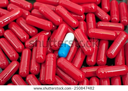 Blue and white capsule among red capsules