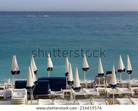 Blue and White Closed Umbrellas and Empty Loungers on a Pebble Beach - stock photo