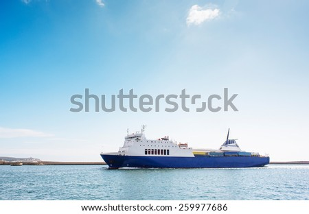 Blue and white container ship at the port of Cagliari, in a clear sunny day - stock photo