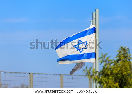 Blue and white flag of Israel waving on strong wind