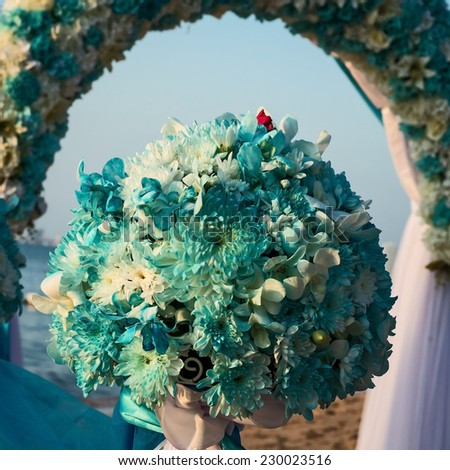 blue and white flowers forwedding arch on the beach - stock photo