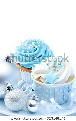 Blue and white icing frosted cupcakes with silver christmas decoration baubles and ribbons on a plate   - stock photo