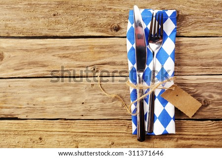 Blue and white place setting in Bavarian colors with a silver knife and fork tied with raffia and a tag on a blue and white napkin on a rustic wooden table with copyspace conceptual of Oktoberfest - stock photo