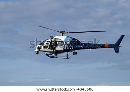 blue and white police helicopter flying in the sky, door is open and a police man is looking down - stock photo
