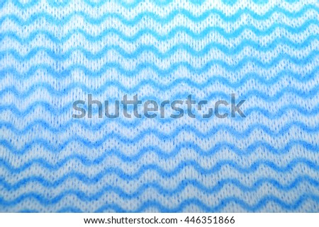 Blue and white sponge cloth (cleaning cloth) with zig zag wavy pattern - stock photo