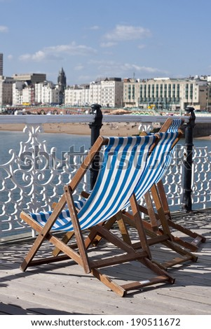 Blue and white striped deckchairs on Brighton Pier facing the beach - stock photo