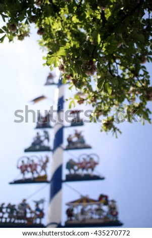 Blue and white striped maypole with traditional decorations in Munich, Germany