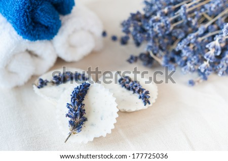 Blue and white towels, lavender bouquet and lavender soap on a linen napkin - stock photo