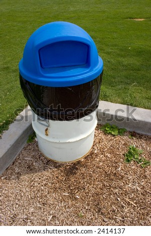 Blue and white trash can at park - stock photo