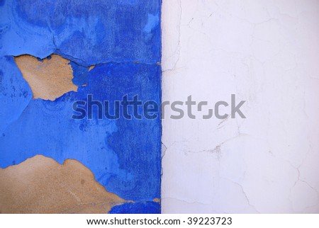 Blue and white wall in a mediterranean country with cracked paint - stock photo