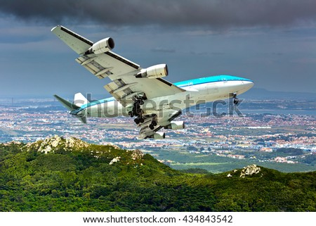 Blue and white wide-body passenger airplane. Aircraft is flying over the city and mountains. - stock photo