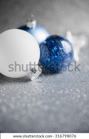 Blue and white xmas ornaments on glitter holiday background. Merry christmas card. Winter holidays. Xmas theme. - stock photo