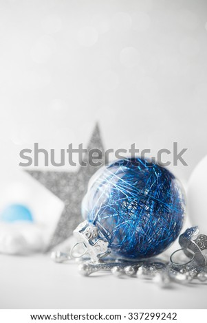 Blue and white xmas ornaments on glitter holiday background. Merry christmas card. Winter theme. Happy New Year. - stock photo
