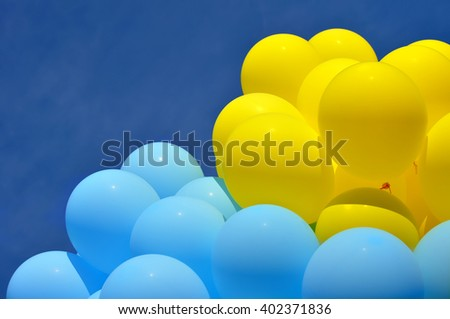 blue and yellow  balloons in the city festival on blue sky background - stock photo