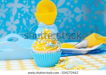 Blue and yellow cupcake setting with empty cups and plateau - stock photo