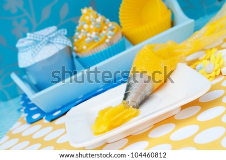 Blue and yellow cupcake setting with whipped cream tool - stock photo