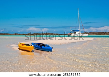 blue and yellow kayaks beached along the white sand beach with catamaran sailboat anchored in the background. - stock photo