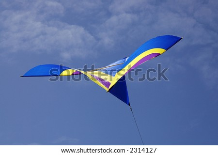 Blue and yellow kite against blue sky