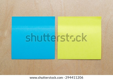 blue and yellow reminder sticky note on wood background - stock photo