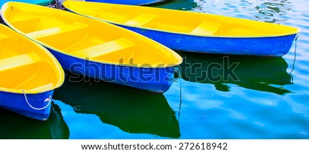 Blue and yellow rowboats anchored at jetty - stock photo