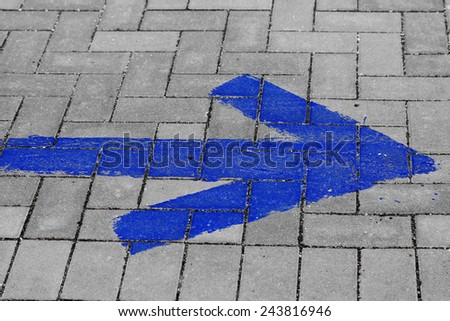 blue arrow on grey paving, pointing to the right.