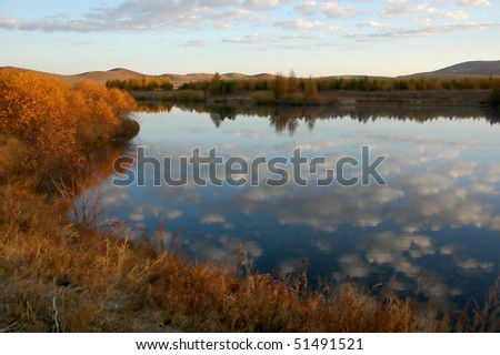 Blue autumn sky and white clouds reflecting in the lake