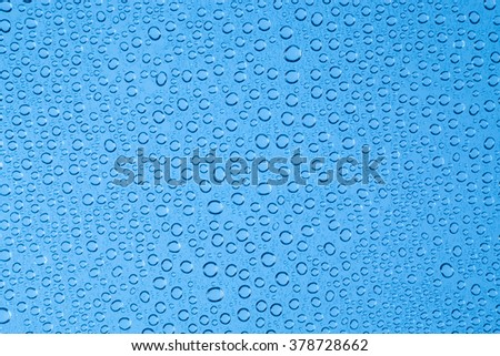 Blue background drops of water on clear glass.
