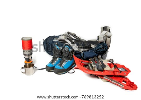 Blue backpack, blue mountaineering boots, red snowshoes and stoves isolated on the white background