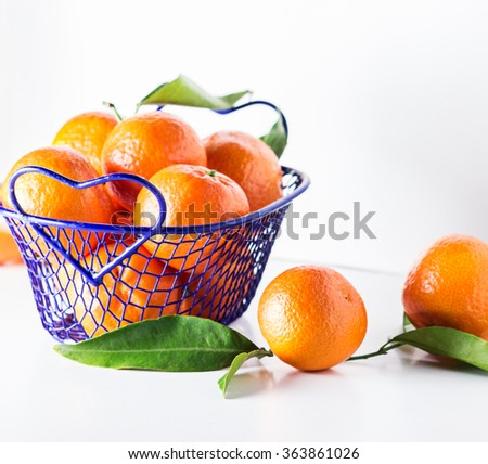 Blue basket full of fresh orange fruits on a white background.