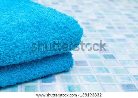 Blue Bath Towels on Bathroom Tiles - stock photo