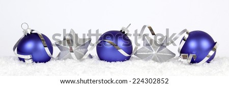 Blue baubles and silver stars on the snow - stock photo