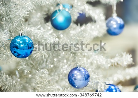 Blue baubles hanging on silver artificial christmas tree, good as background - stock photo