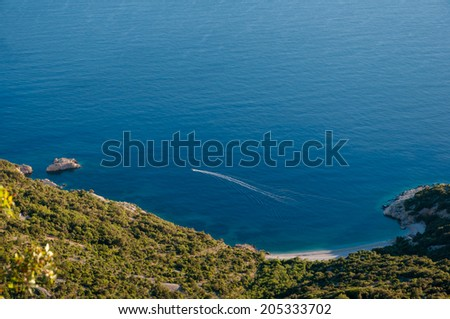 Blue bay and boat under Lubenice town in Cres - Croatia - stock photo
