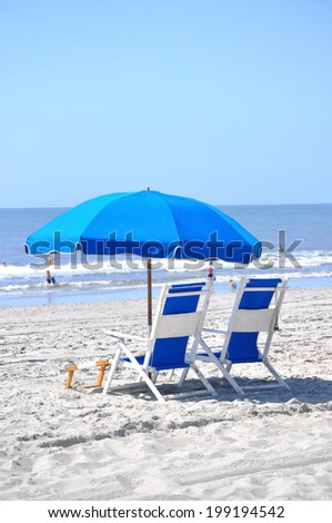 Blue beach chairs and umbrella on the beach - stock photo