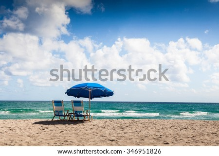 Blue beach chairs on the sand beach with cloudy blue sky and sun,relax  - stock photo