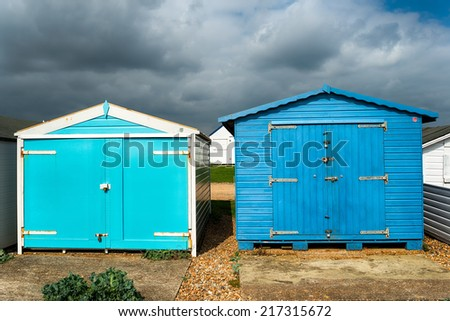 Blue beach huts under a dramatic sky at St Leonards on Sea in Hastings, East Sussex - stock photo