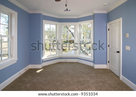 blue bedroom with lots of windows looking out onto pond - stock photo