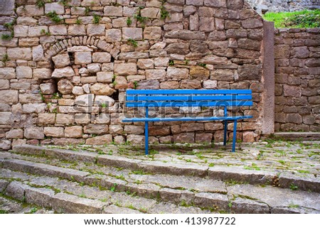 Blue bench next to the stones wall in labin - stock photo