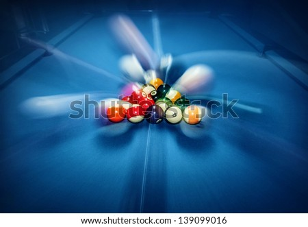 Blue billiard table with colorful balls, beginning of game, slow motion, soft focus, snooker bar, entertainment in nightclub, hobby and sport concept - stock photo