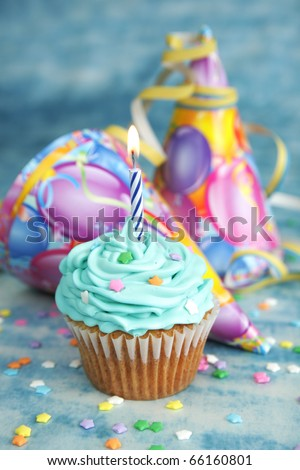 Blue birthday cake with candle on top and hat in the background - stock photo