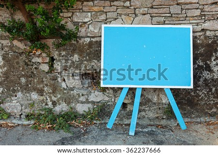 Blue blank signboard standing near old stone wall, copy space for your text - stock photo