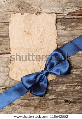 Blue bow on blank old paper with copy space for your text - stock photo